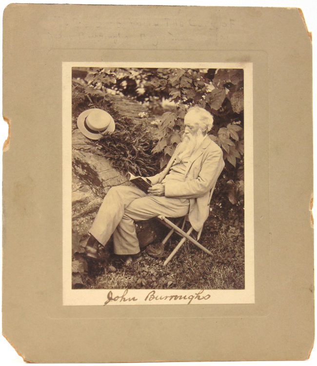 An excellent photograph of John Burroughs, seated, reading, next to a large rock and tree with his straw hat laid on the ferns. John Burroughs.