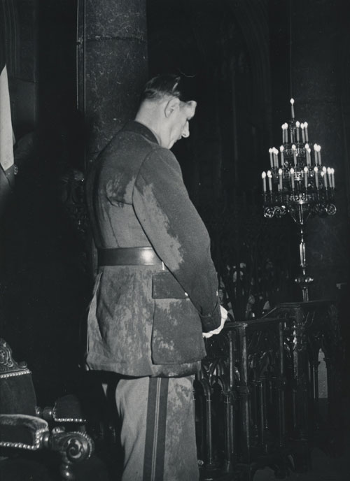 Photograph of a rain-soaked Charles de Gaulle praying in the Cathedral of Notre Dame, Nice, 1948. Charles De Gaulle, Dmitri Kessel, photographer.
