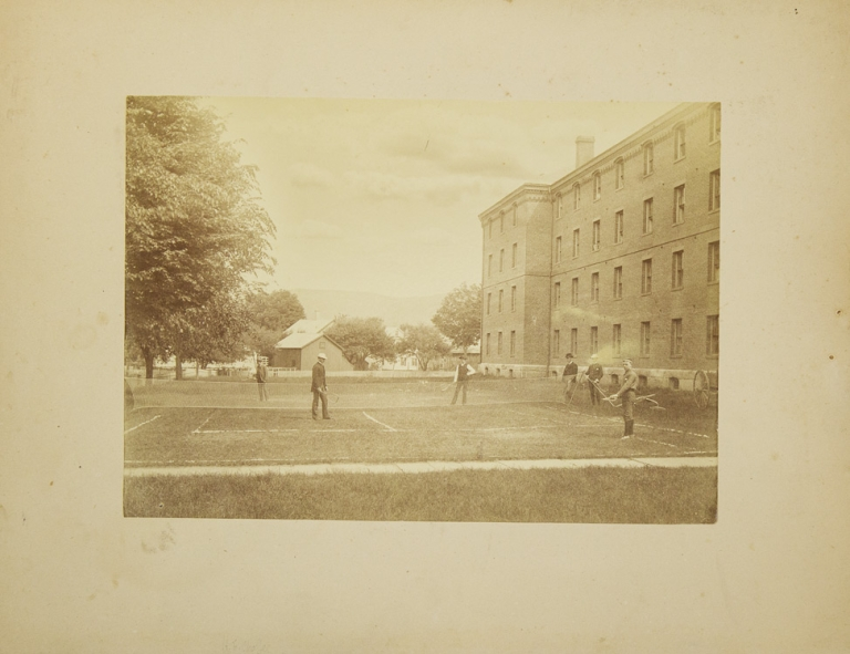 "Photograph of a doubles lawn tennis match, with 2 observers and a large brick building and ""penny-farthing"" high-wheel bicycle at right. Tennis."