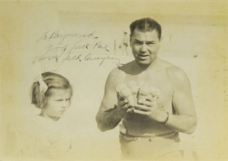 Autographed photo of Jack with 8 ice cream cones in hand at the beach in swim suit with little girl at his side. Jack Dempsey.