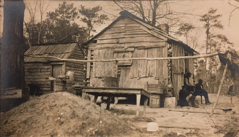 Photograph of three black men sitting outside clapboard-covered log cabin and shed