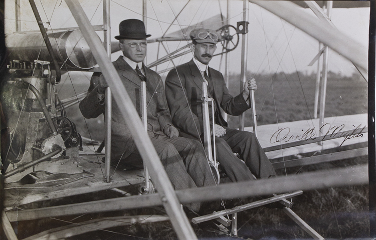 Photograph of Orville Wright with Major Albert B. Lambert seated in the Wright Flyer, 1910, signed by Orville Wright at the right area of the image. Aviation, Orville Wright.