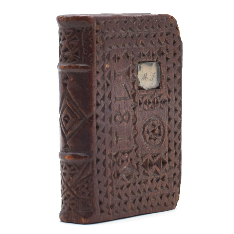 Chip-carved wooden book-form, dated 1781 on upper cover with small inlaid manuscript initials M.J. under glass, with 4 holes hand-drilled into the top likely for use as a quill holder. Folk Art.
