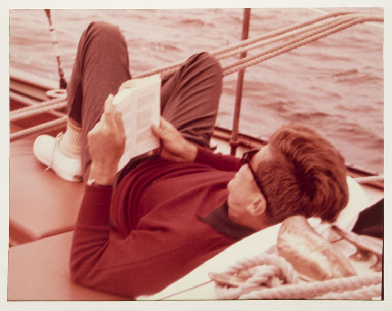 Color Photograph of the President lying on a sailboat, reading , presented to Evelyn Lincoln, the late Presdident's Secretary; with accompany Autograph Letter Signed from Senator Muskie, presenting the photograph; and the retained copy of Mrs. Lincoln's letter of thanks to Muskie. John Fitzgerald Kennedy, Edmund Muskie, Senator.