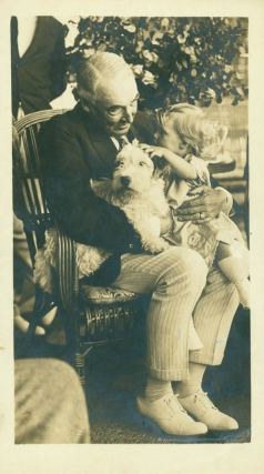 Photograph of the elderly Harding dandling a little girl on his knees, with her dog. Warren G. Harding, photographers, Underwood, Underwood.
