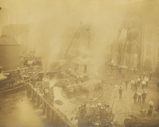 Firefighting scene showing dockside building on fire, being put out by hose and ladder apparatus of four fire engines, with spectators