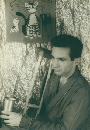 "Portrait photograph of Ben Gazzara as ""Brick"" in CAT ON A HOT TIN ROOF, seated in robe clutching a drink, crutches in background. Ben Gazzara, Carl Van Vechten."