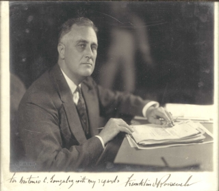 Photographic Portrait of the President at his desk, signed in ink below, as President, and...