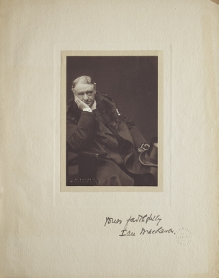 Portrait photograph of author Ian Maclaren, three-quarters length seated, in jacket with top hat in hand. Elias Goldensky.