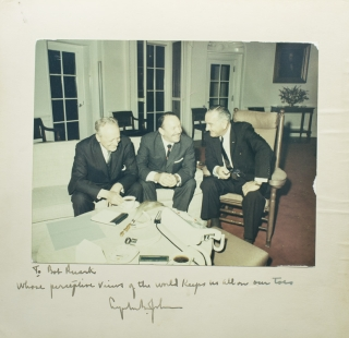 "Photograph of the President, seated in a chair beside author Robert Ruark and another official, before a table of African souvenirs, Inscribed ""To Bob Ruark, whose perceptive views of the world keeps [sic] us all on our toes, Lyndon B. Johnson"" Lyndon B. Johnson."