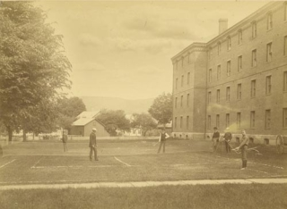 "Photograph of a doubles lawn tennis match, with 2 observers and a large brick building and ""penny-farthing"" high-wheel bicycle at right"