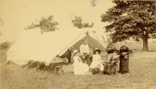 [The Earle Camp at Bullòn Woods] Photograph of tennis players (two ladies seated, two men standing) at ease near a tent, the net just visible to the right. Tennis.