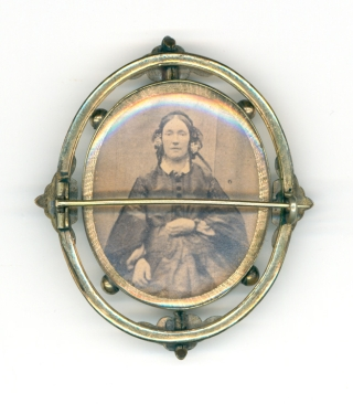 Tintype and albumen portrait photographs of a women housed in a double-sided brooch