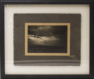 Photograph of Wilbur Wright in a Wright Flyer at twilight