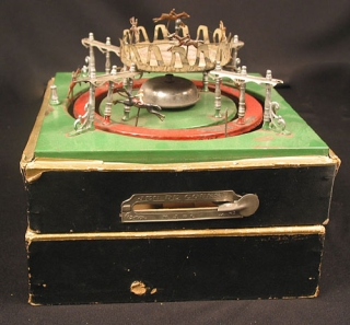 "Game: ""Jeu de Course"" in original black wooden box with metal spring loaded handle. 6 Horses (one missing) on circular colored metal courses with 4 metal sets of 3 poles. Horses Racing Game."